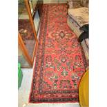 Sarouk style runner with all-over floral design on a red ground with borders, 112ins x 40ins