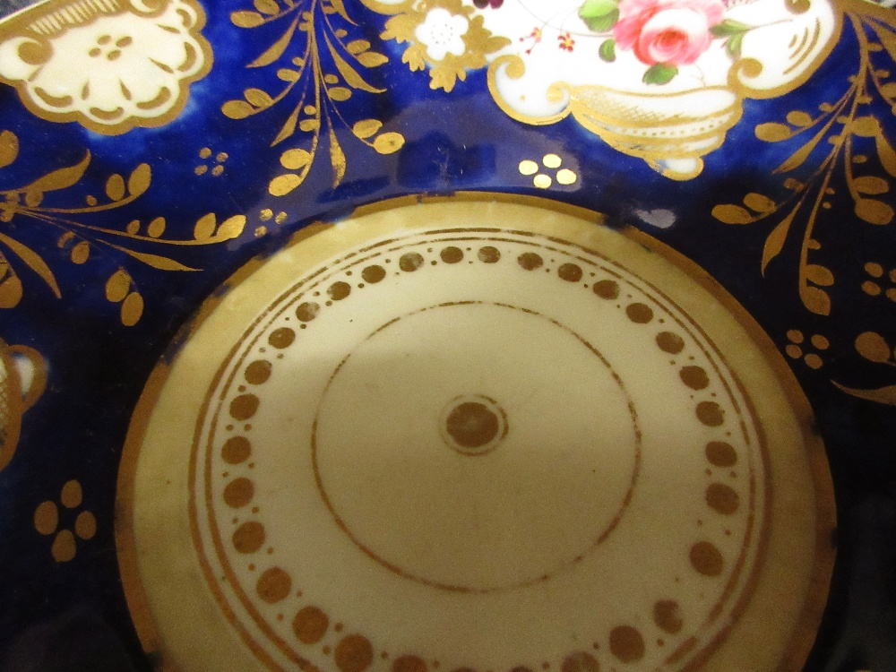 Lot 680 - Three 19th Century English tea cups with saucers decorated with panels of flowers on cobalt blue and