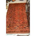 Belouch rug having a line of four gols with multiple borders on a rust ground, 5.5ft x 4ft, together