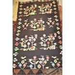 Kelim rug of floral design on black ground, together with another Kelim rug on blue ground Black