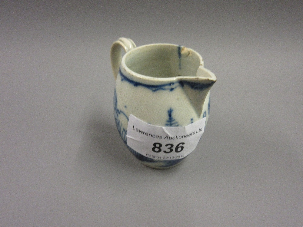 Lot 836 - 18th Century English blue and white oviform miniature jug, decorated with stylized flowers in a