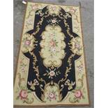 Small Aubusson type needlepoint rug with floral design on a black ground, 59ins x 36ins