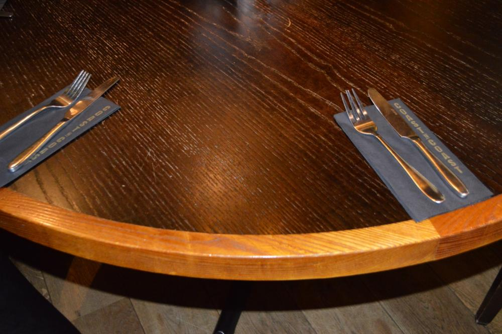 Lot 160 - 4 x Restaurant Dining Tables With Cast Iron Bases - Two Tone Wooden Finish With Shaped Edges - H76 x