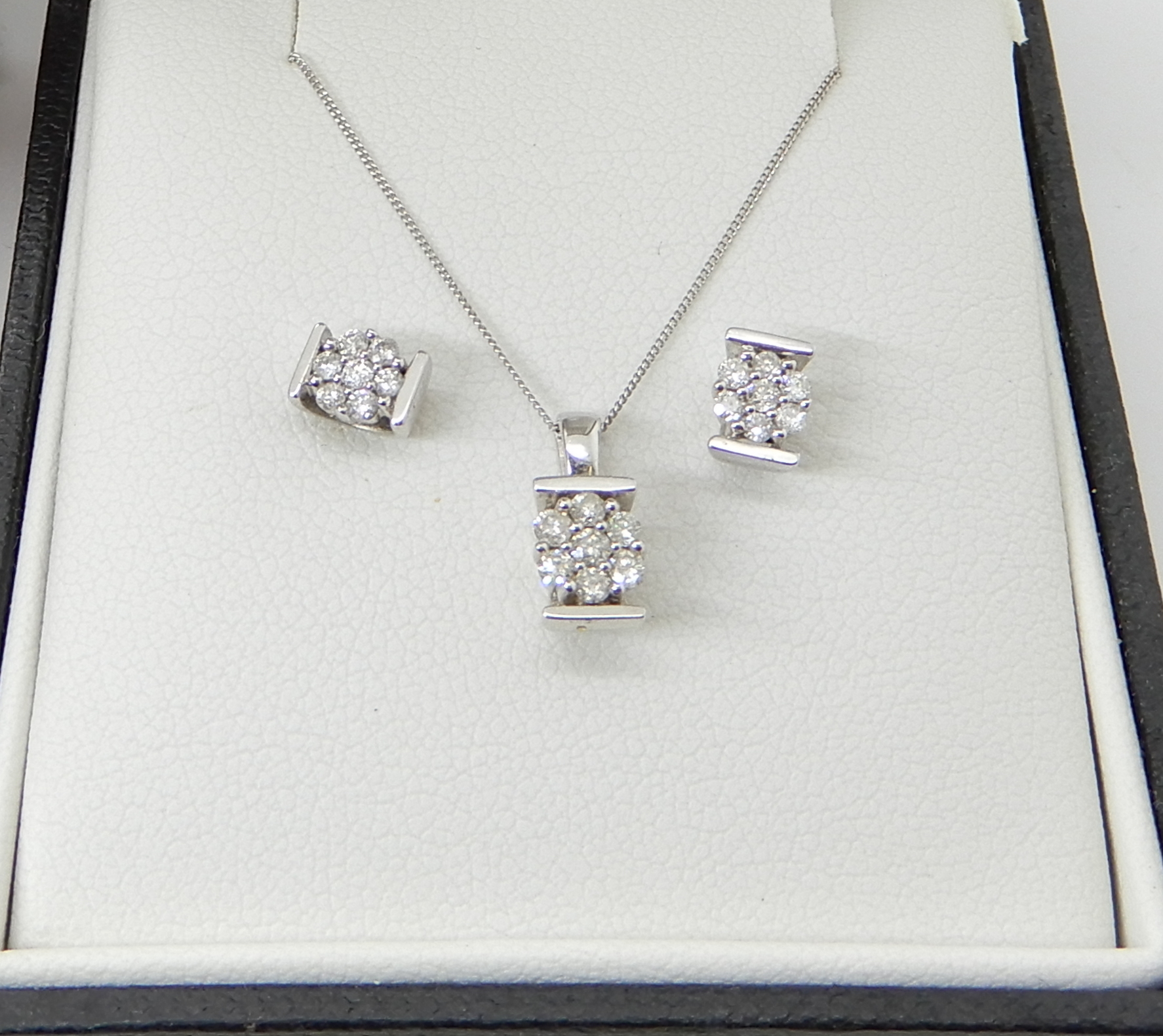 A 9ct white gold flower pendant and chain and a pair of matching earrings, set with estimated approx