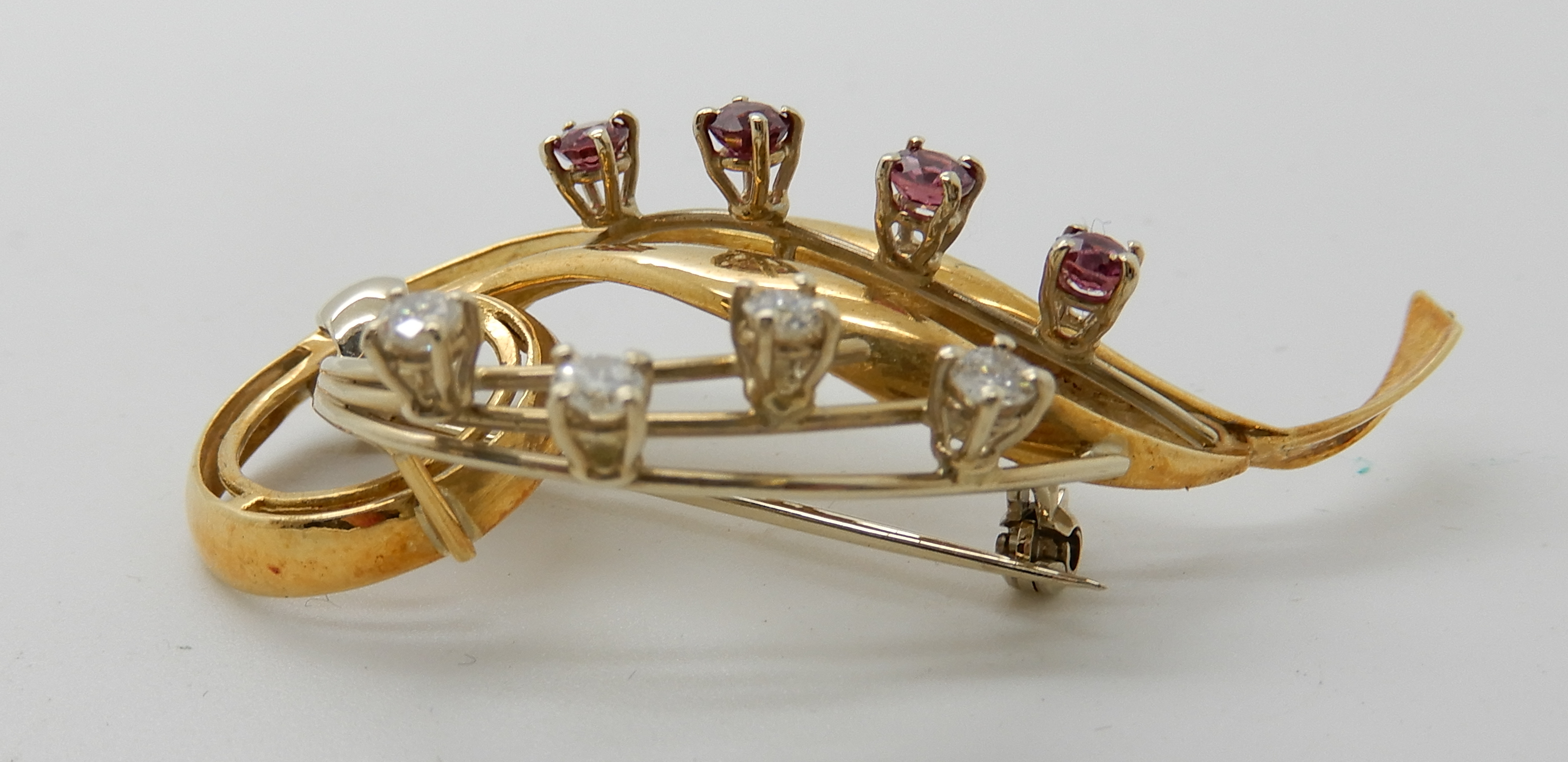 Lot 35 - An 18ct gold ruby and diamond brooch, diamond content estimated approx 0.34cts, length 5.2cm, weight