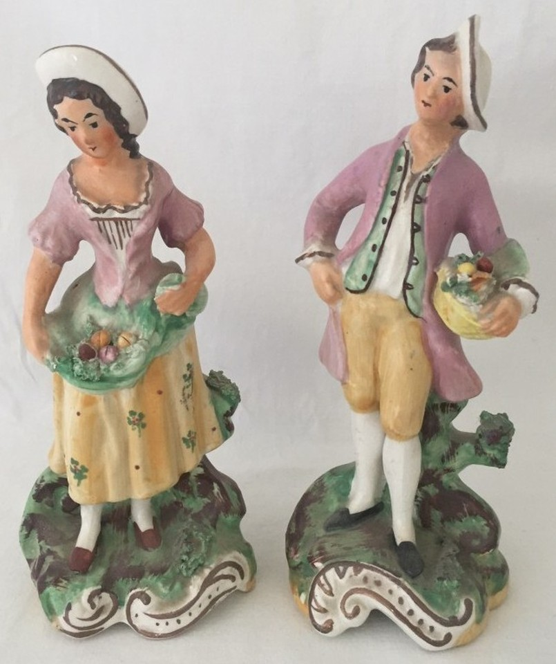 Lot 91 - A pair of Victorian ceramic figurines of a man and woman holding baskets of fruit.