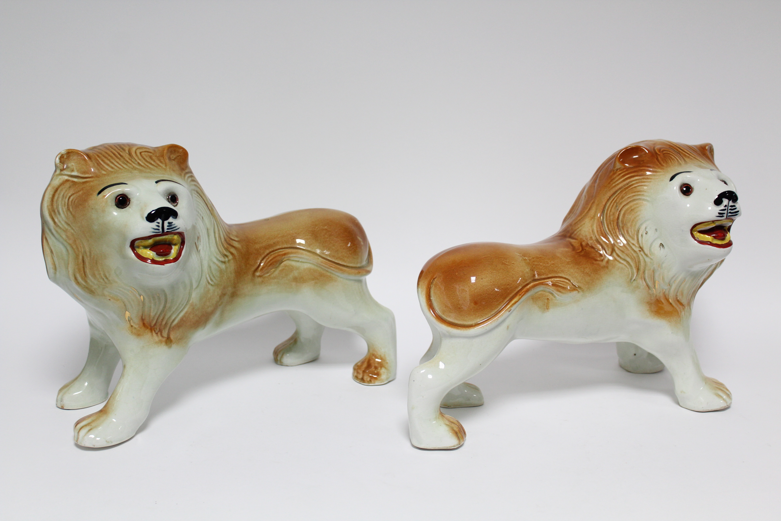 Lot 53 - A pair of early 20th century Sadler Pottery large standing models of roaring lions with inset