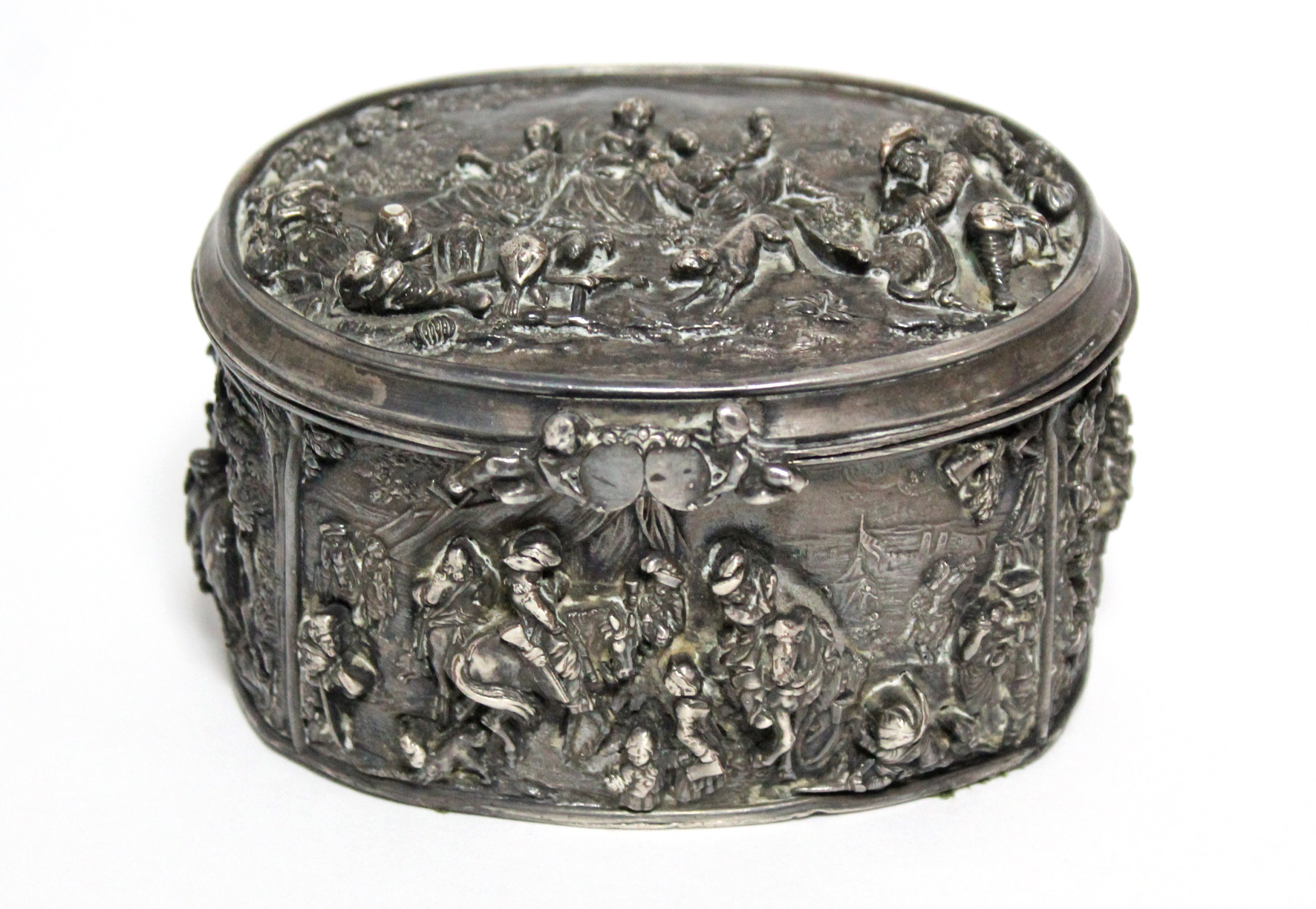 A continental white metal oval box, decorated in relief with scenes of huntsmen, figures & animals