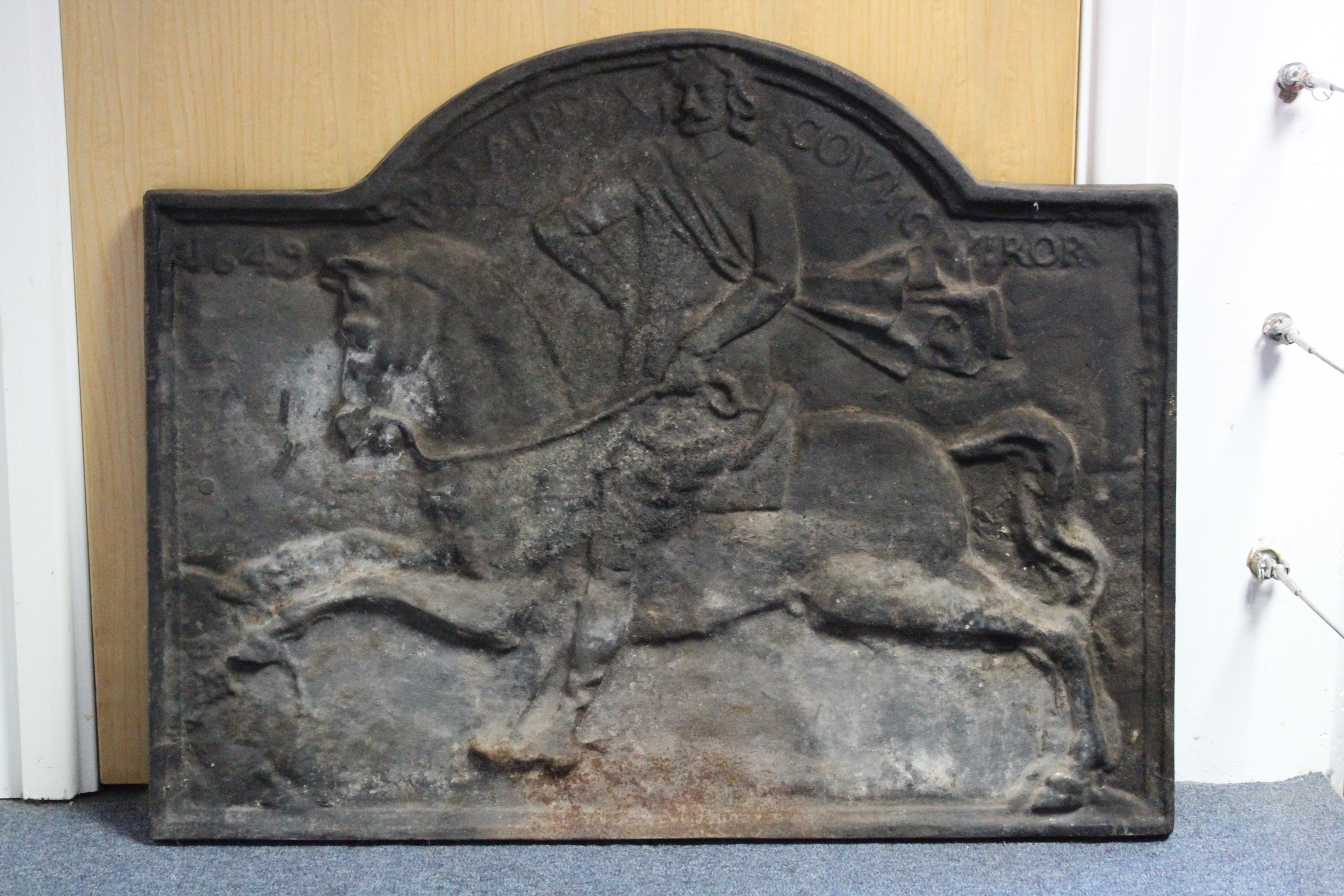 Lot 155 - A 17th century-style cast-iron fireback with shaped top & scene of a man on horseback, dated 1649;