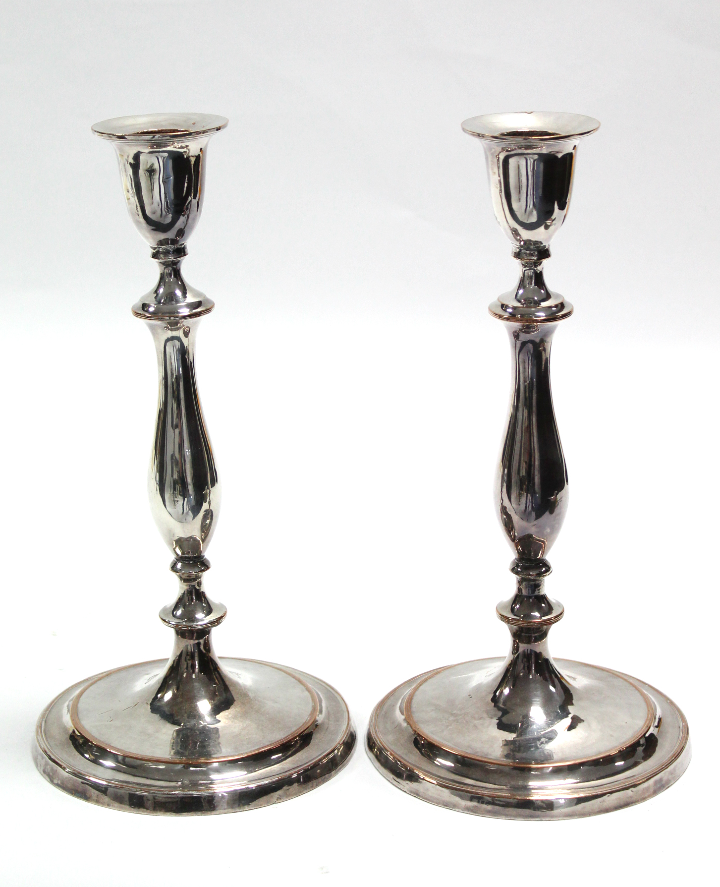 A pair of late 18th century Sheffield candlesticks with vase-shaped nozzles, slender baluster
