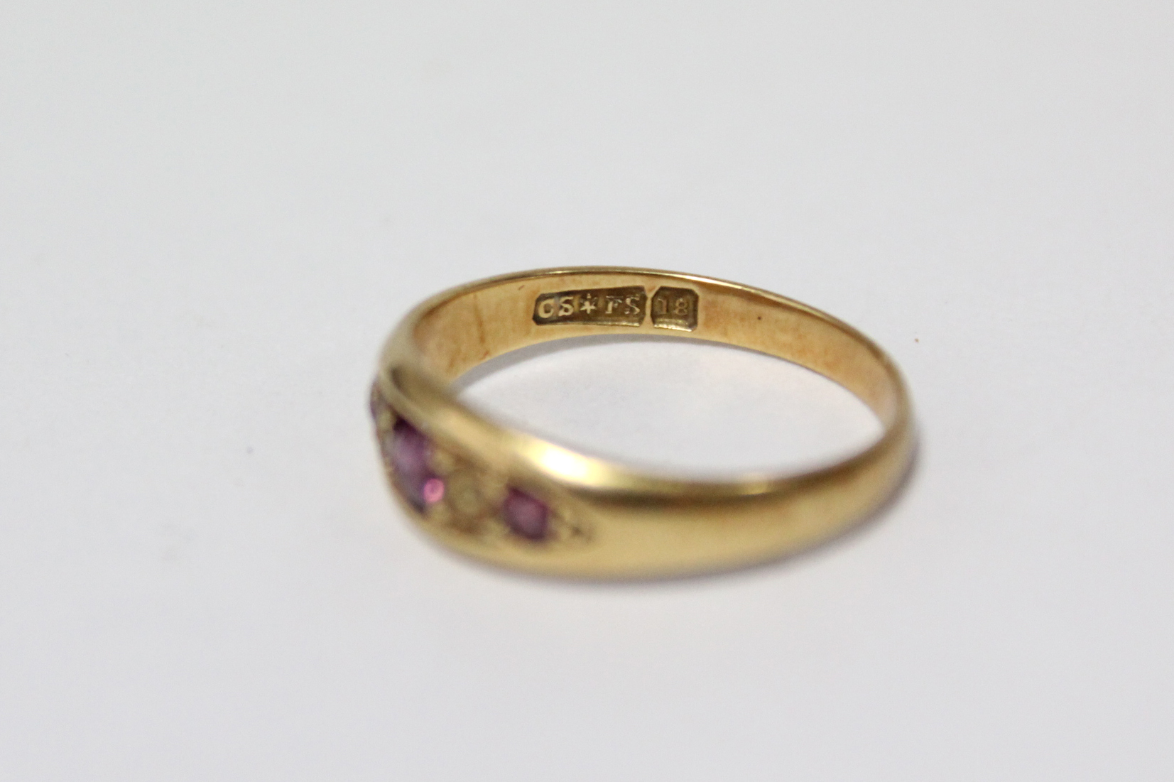 Lot 40 - An 18ct. gold ring set three small graduated rubies (2.1gm); a 15ct. gold & seed-pearl Christian