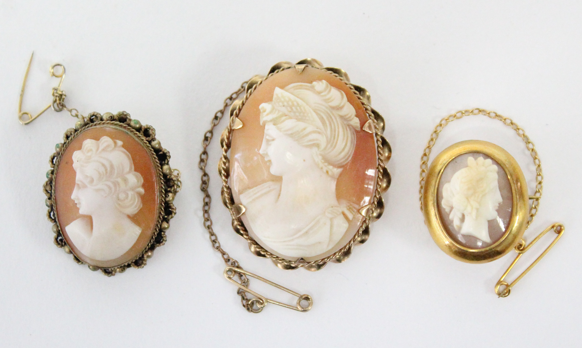"""A carved shell oval cameo brooch depicting a female portrait, in 9ct. gold mount, 1½"""" x 1""""; & two"""