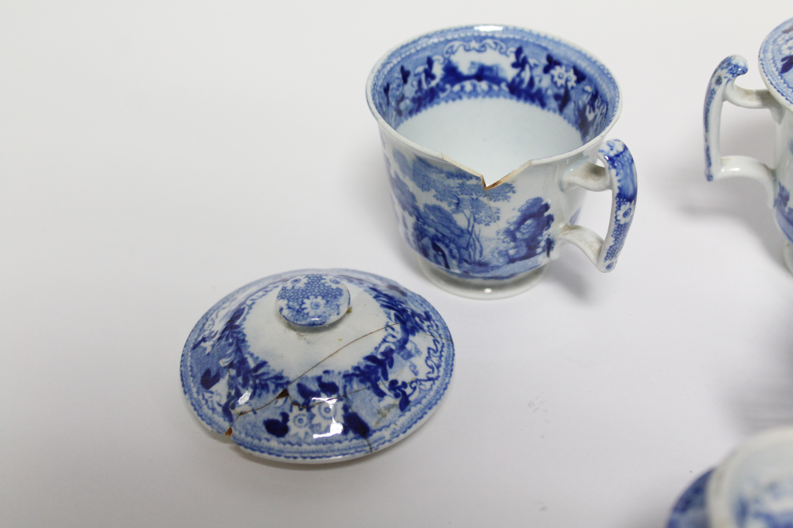 Lot 54 - A set of six early 19th century blue transfer custard cups & covers, each decorated with scenes from