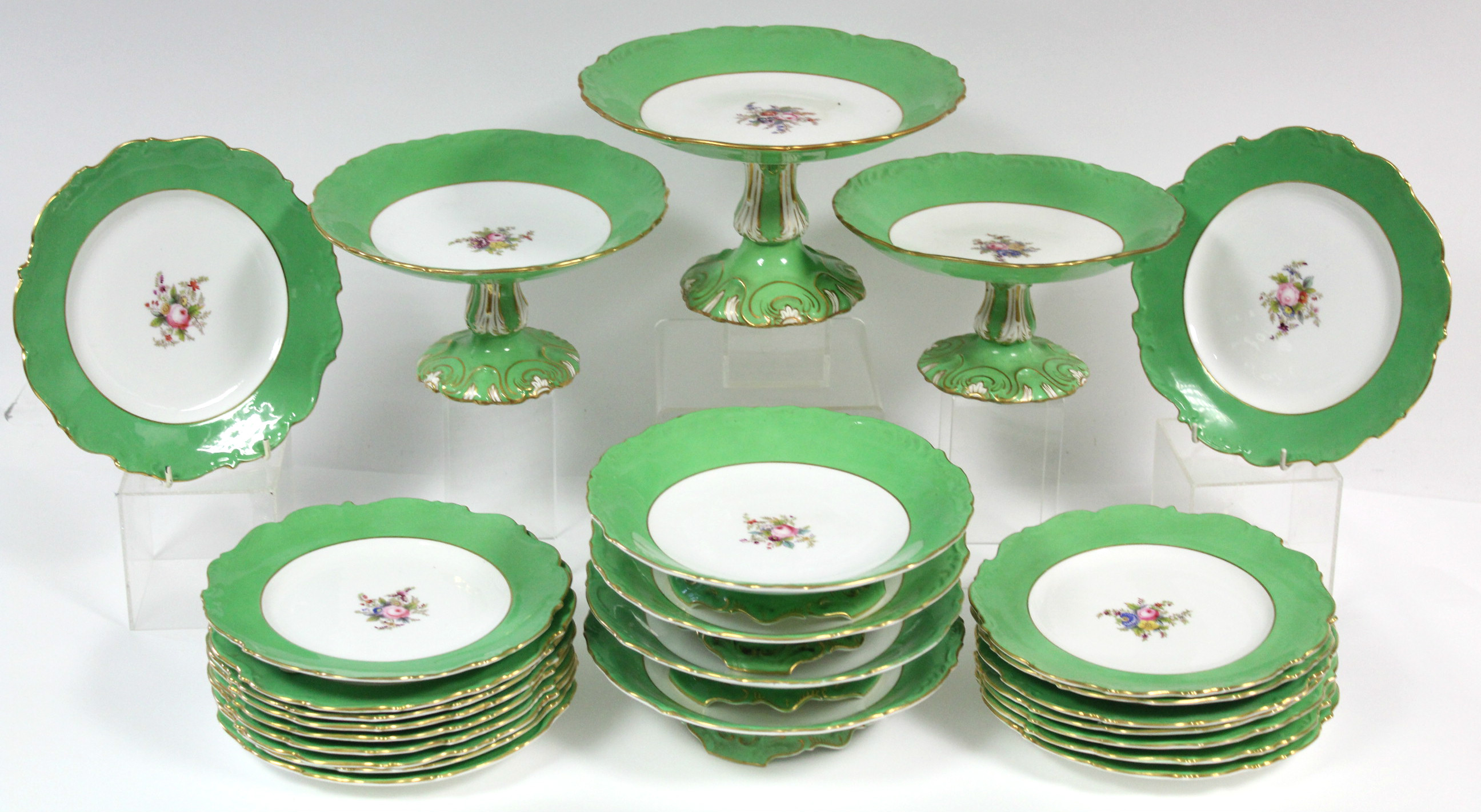 Lot 50 - A Coalport porcelain dessert service with wide apple-green borders & moulded gilt rims, each piece