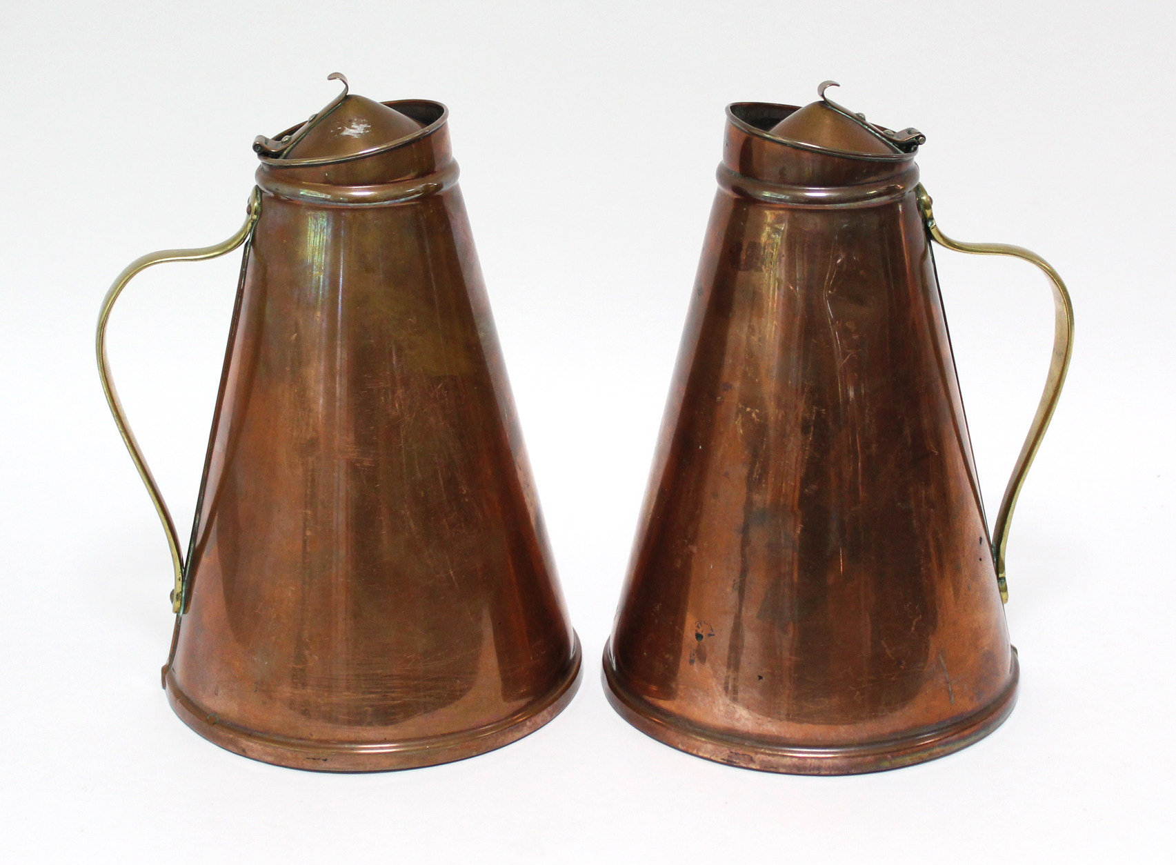 """Lot 163 - A pair of W. A. S. Benson Arts & Crafts copper """"Jacketed Jugs"""" of tapered cylindrical form, with"""