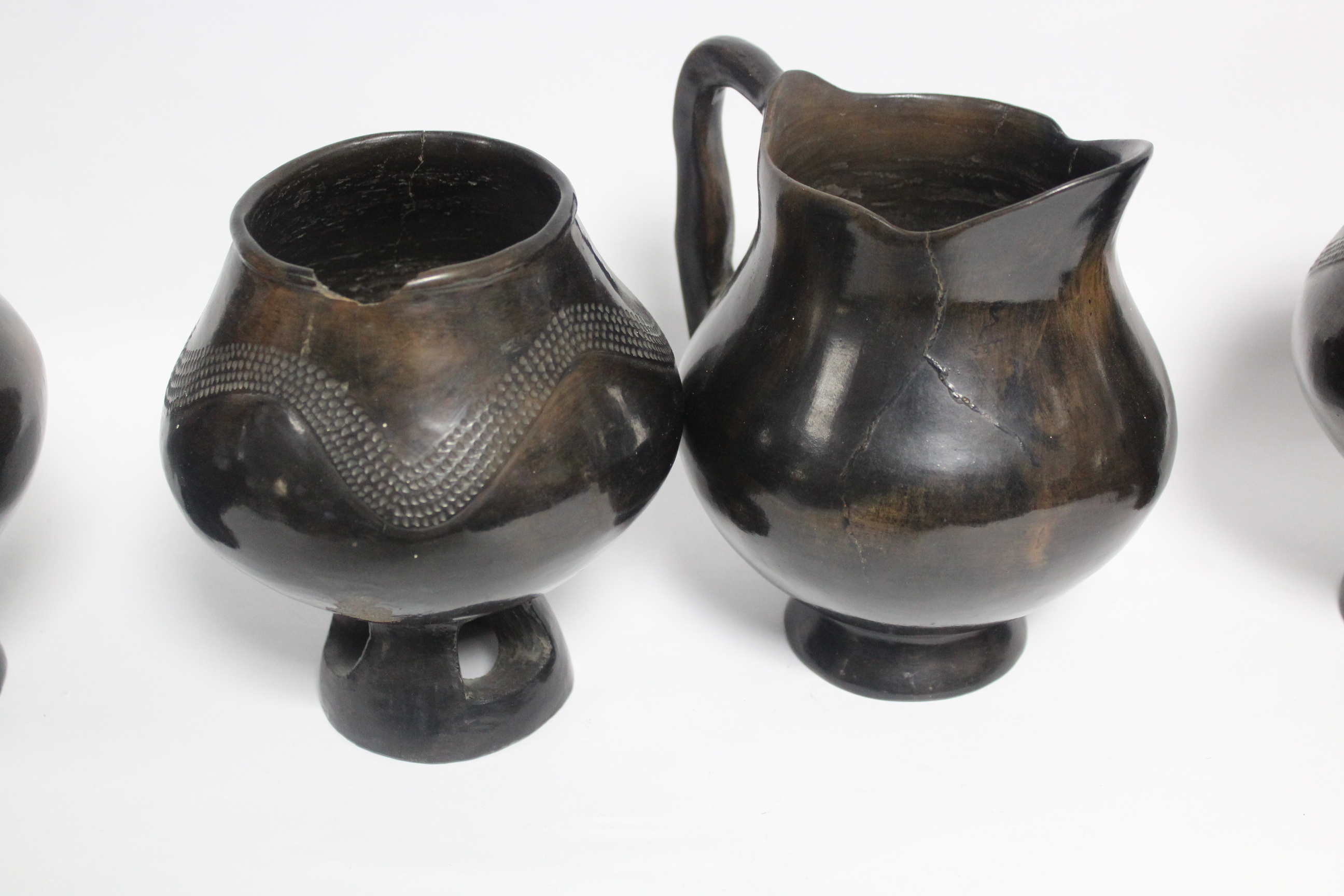 "A group of four dark brown glazed earthenware vessels, each on pierced foot, 6"" high; & a similar - Image 2 of 2"