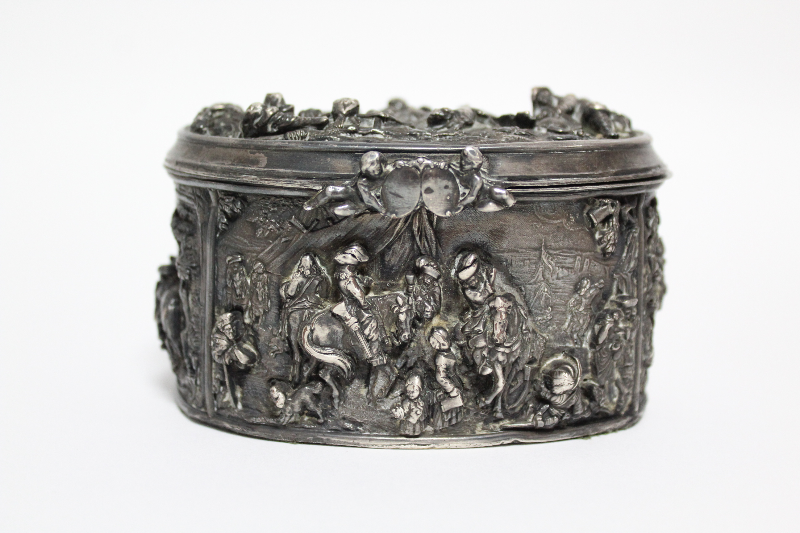 A continental white metal oval box, decorated in relief with scenes of huntsmen, figures & animals - Image 2 of 9
