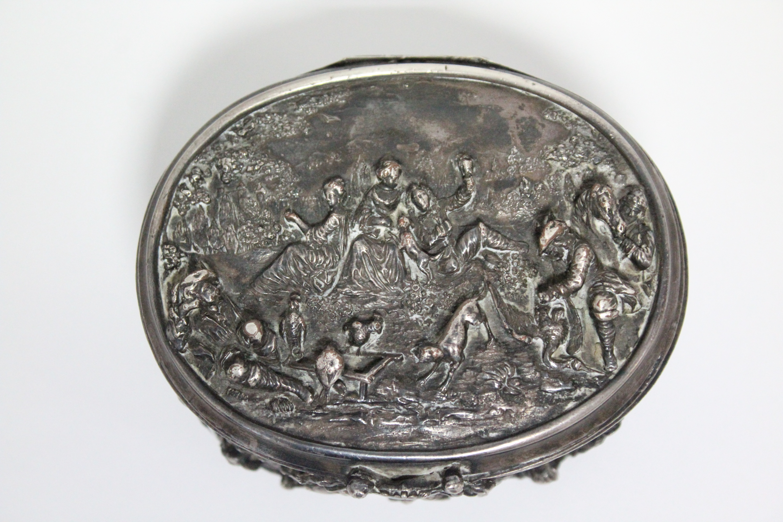A continental white metal oval box, decorated in relief with scenes of huntsmen, figures & animals - Image 6 of 9