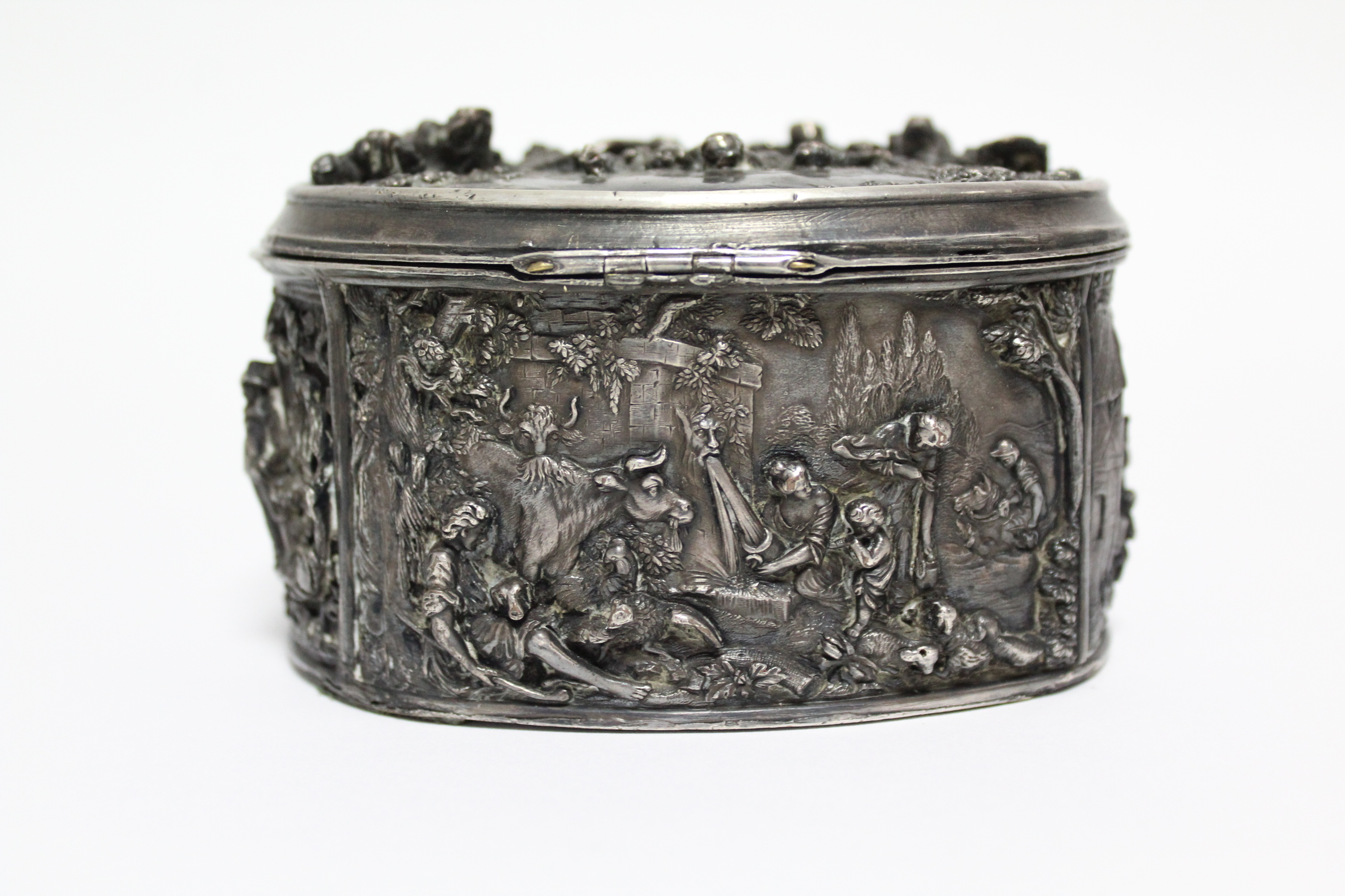 A continental white metal oval box, decorated in relief with scenes of huntsmen, figures & animals - Image 3 of 9