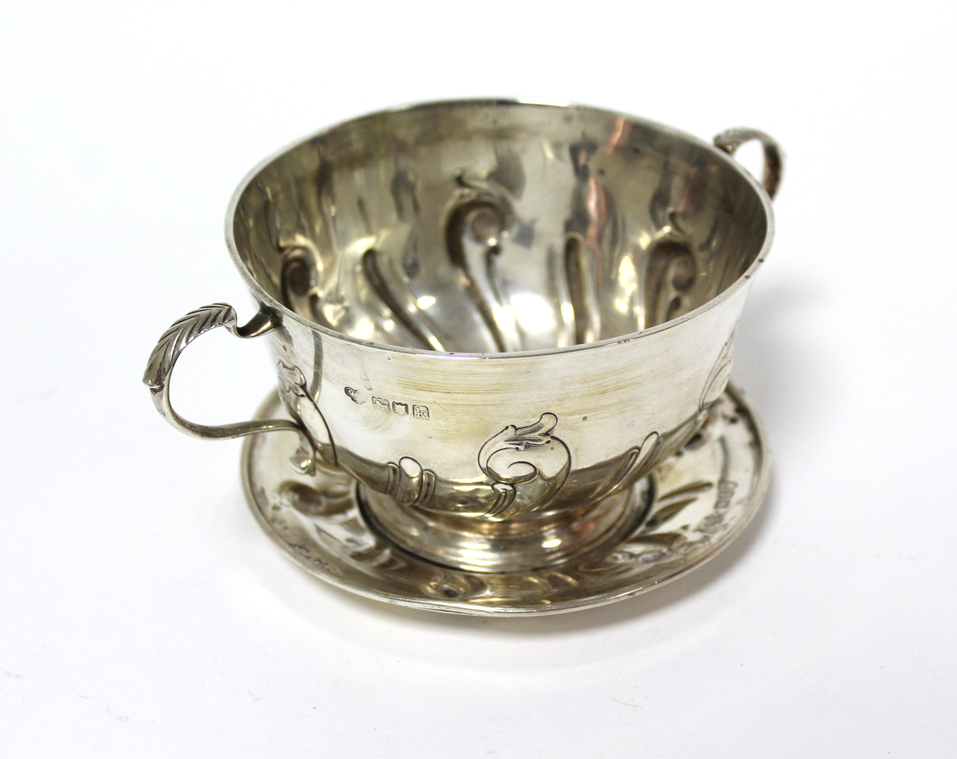 An Edwardian two-handled porringer & paten, both with embossed scroll decoration; London 1905 by