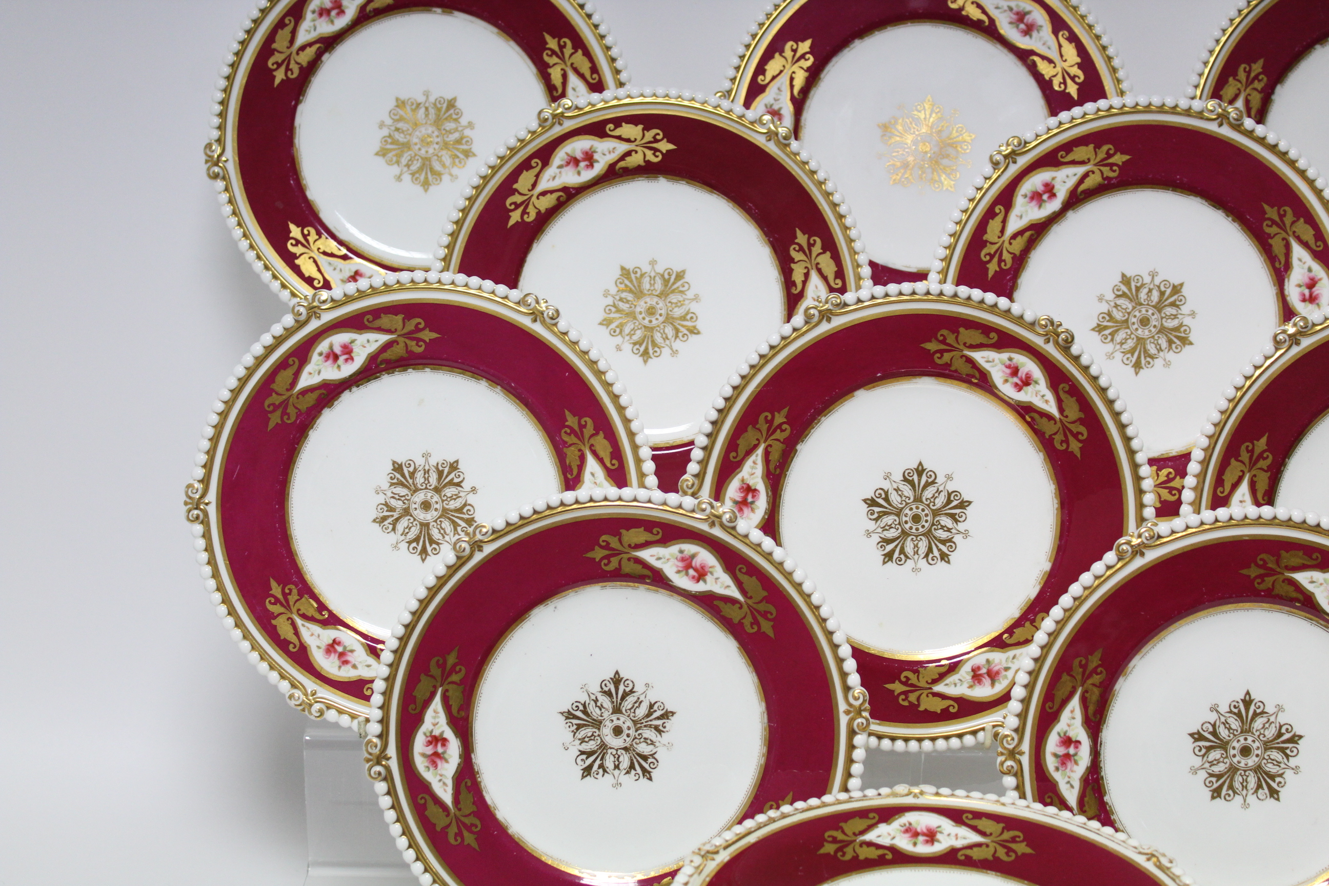 Lot 57 - A Victorian dessert service with beaded rims, reserves of pink roses to the wide ruby & gilt