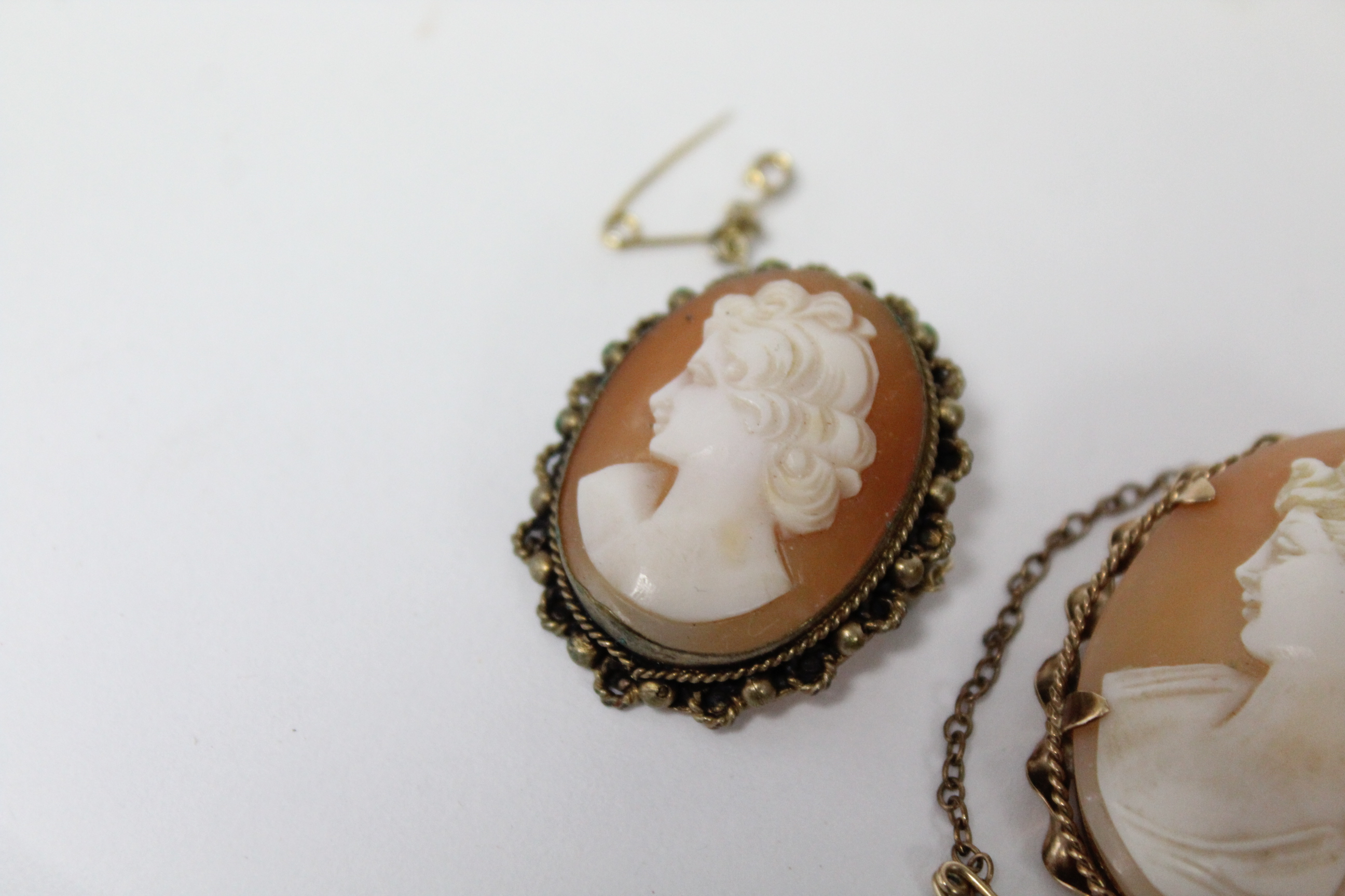 "Lot 39 - A carved shell oval cameo brooch depicting a female portrait, in 9ct. gold mount, 1½"" x 1""; & two"