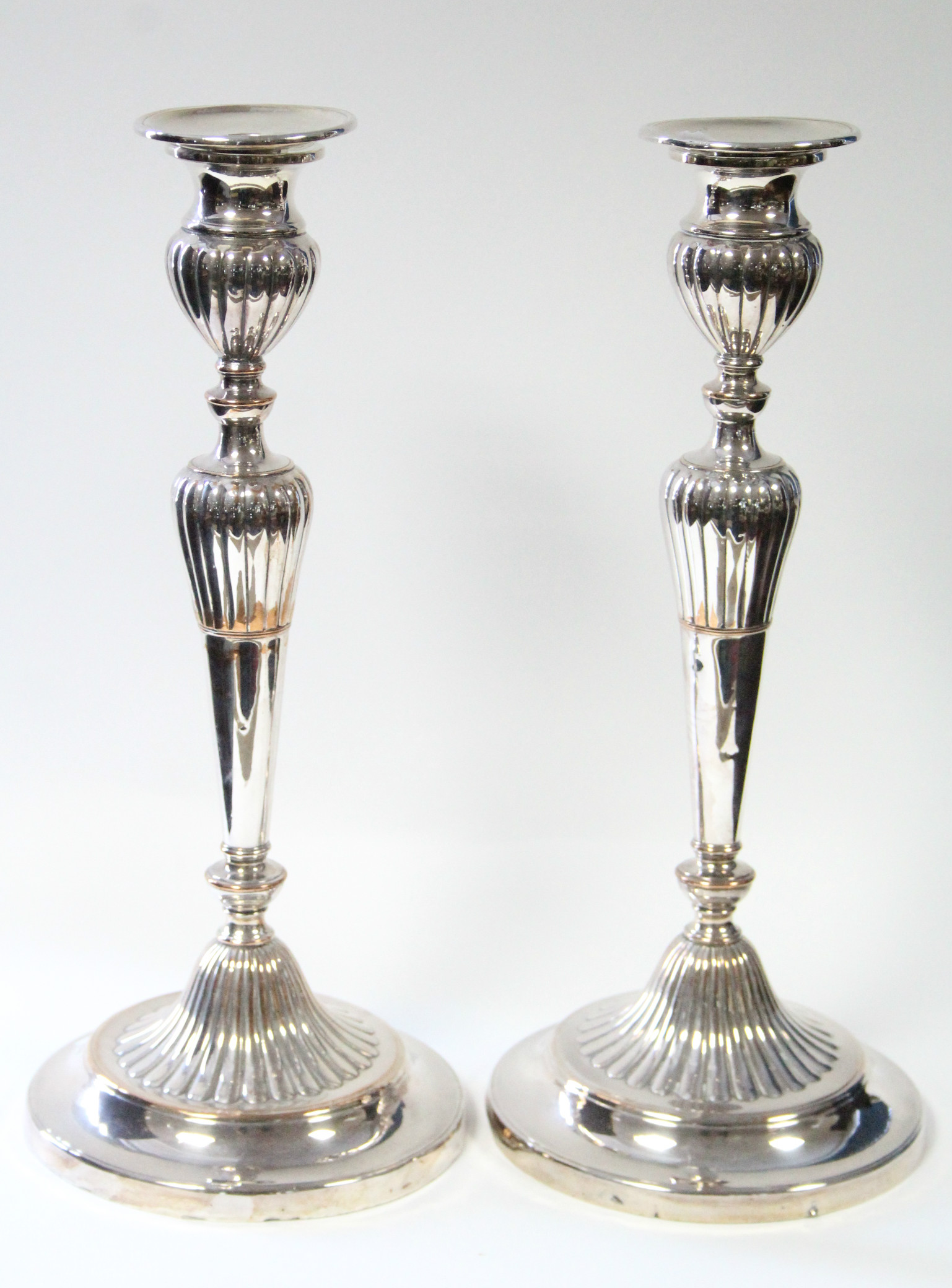 """Lot 2 - A pair of Sheffield candlesticks with part-reeded round tapered columns on circular bases; 12½"""""""