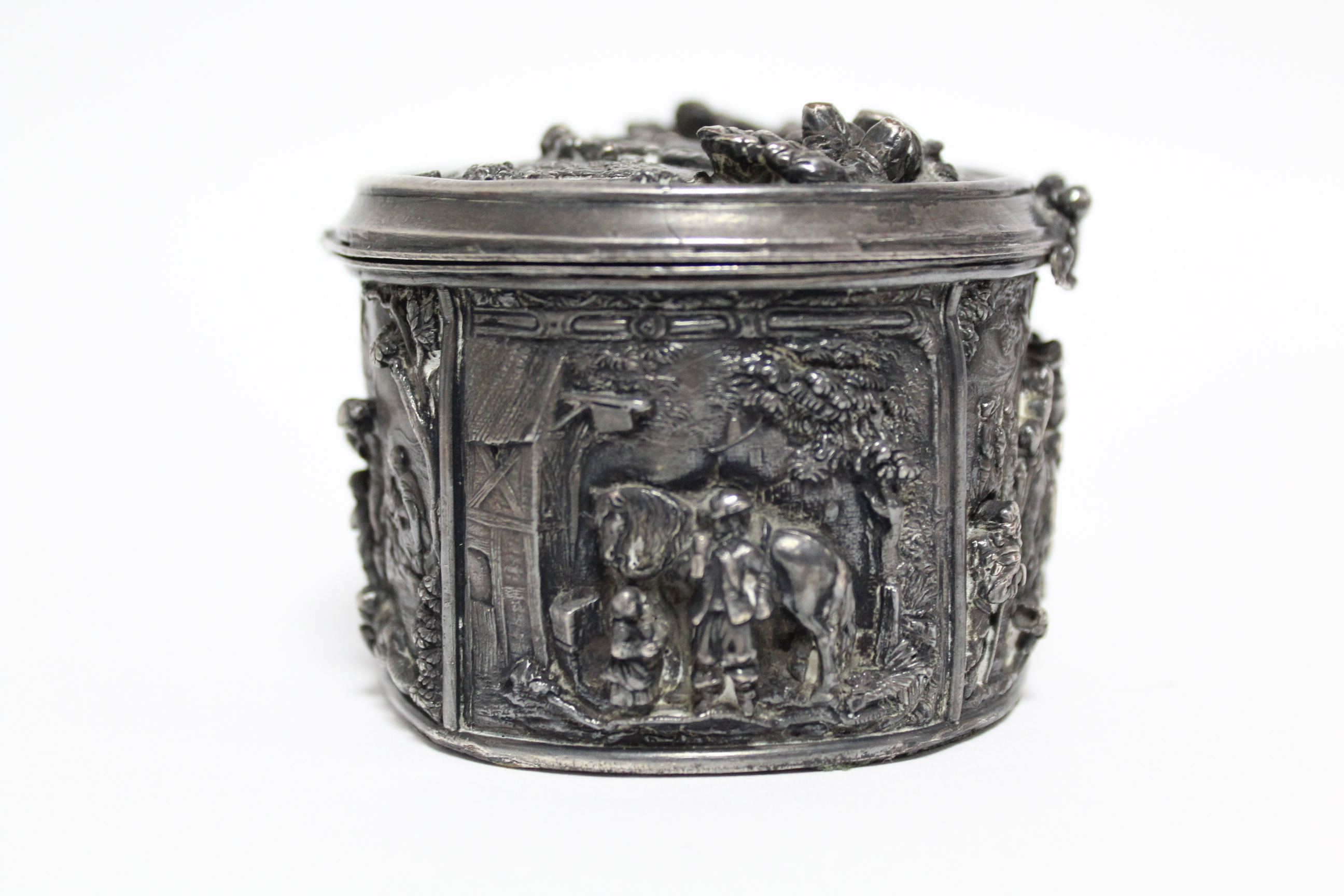 A continental white metal oval box, decorated in relief with scenes of huntsmen, figures & animals - Image 5 of 9