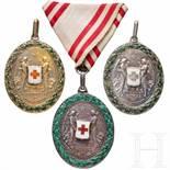Three Red-Cross medalsDrei Ehrenmedaillen in Silber mit Kriegsdekoration. Eine am Dreiecksband, eine