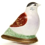 In the form of a bullfinch sitting on a green bunch of reeds the base with a iron red transfer print
