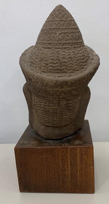 Lot 483 - Cambodian stone head mounted on wood plinth