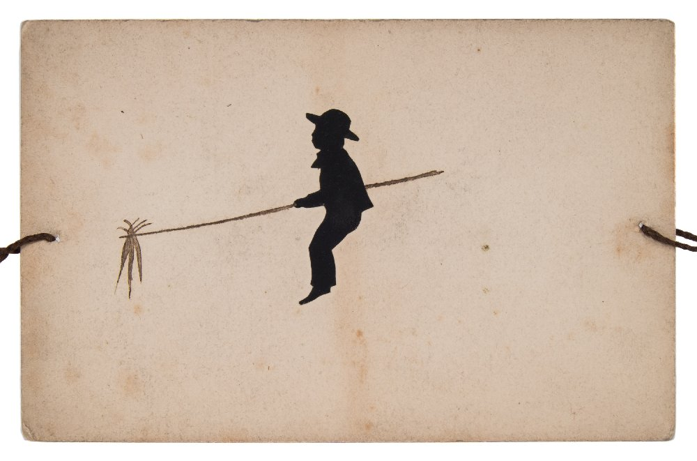 Lot 30 - A hand cut silhouette and ink thaumatrope of a boy with carrots on a stick riding a donke:,