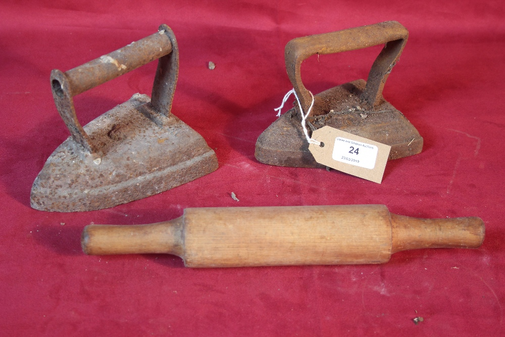 Lot 24 - Two old flat irons and a wooden rolling pin