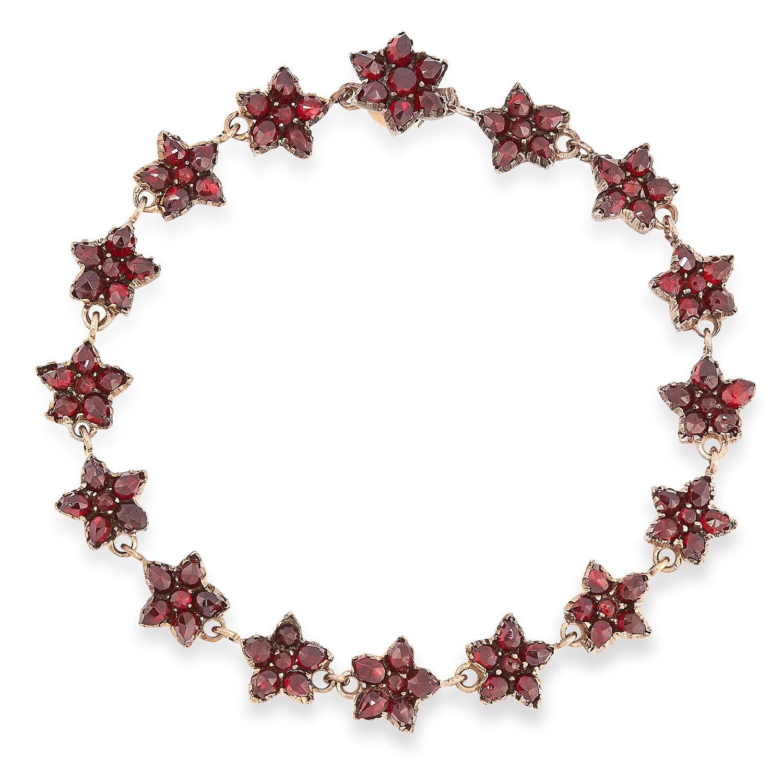 Los 41A - AN ANTIQUE GARNET BRACELET, 19TH CENTURY comprising a single row of floral cluster motifs set with