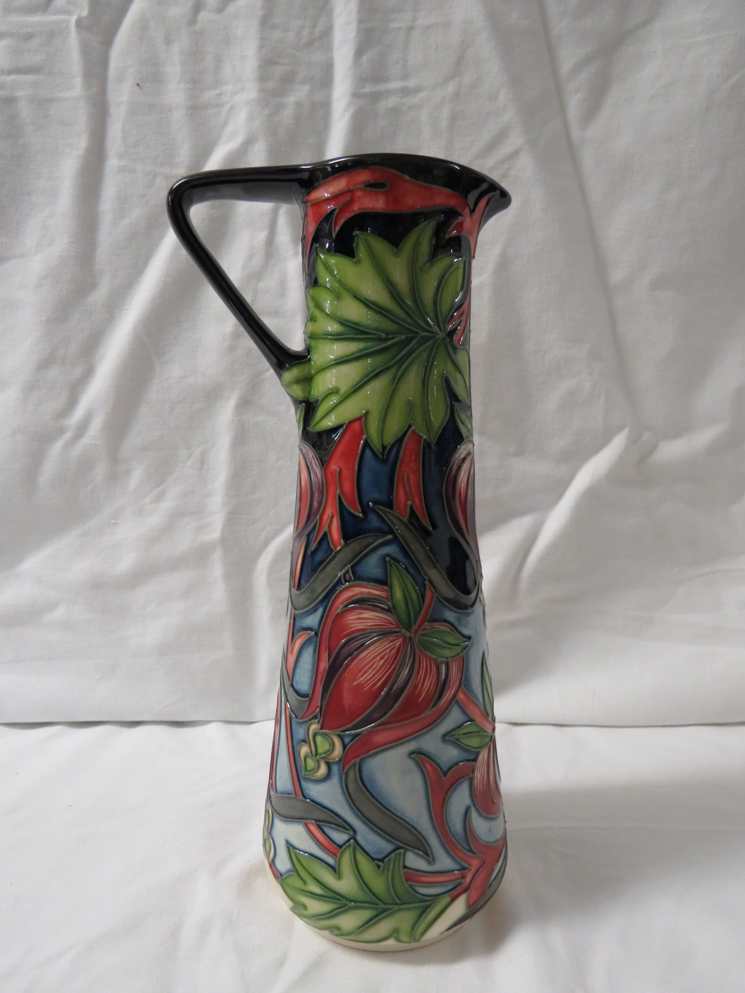 Lot 22 - Moorcroft pottery two star members ewer of tapering cylindrical form with angular handle, dark