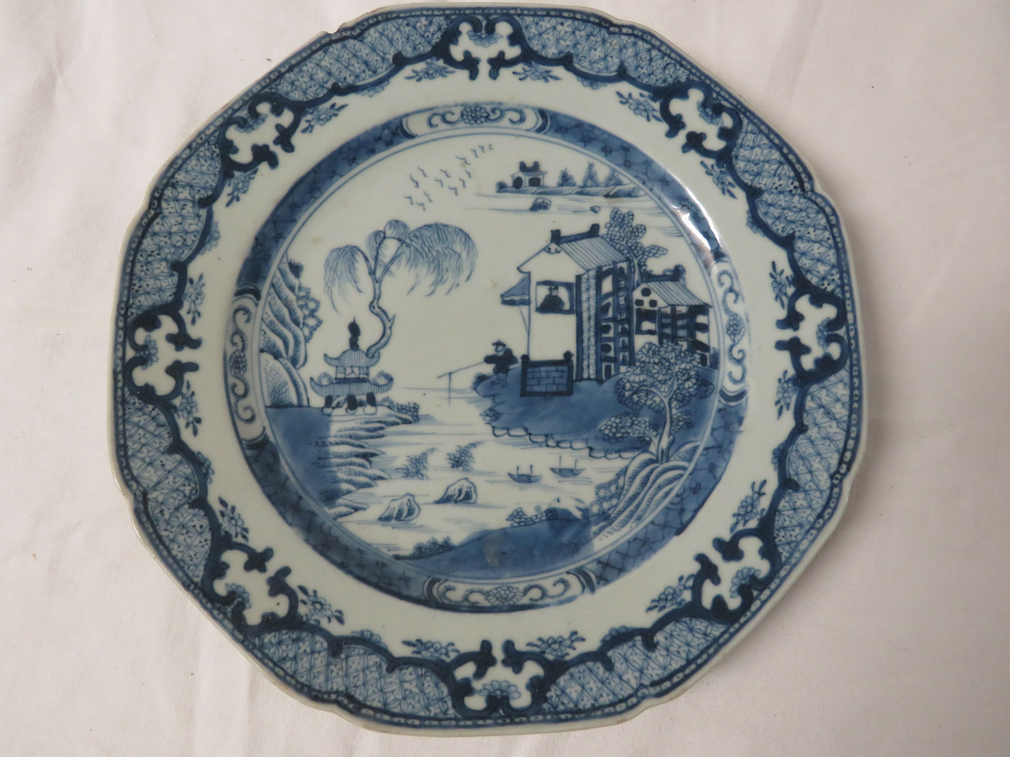 Lot 49 - An octagonal Chinese blue and white porcelain plate painted with houses in landscape and a patterned