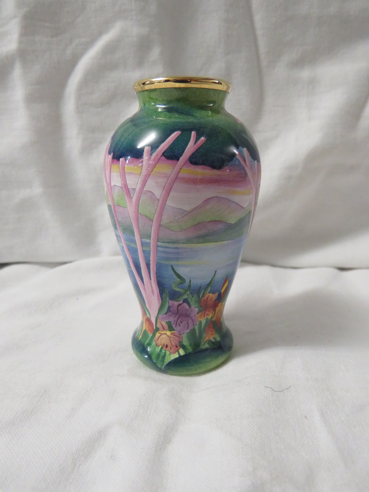 Lot 31 - Moorcroft enamel baluster vase, continuous landscape with trees, hills and irises, gilt rim,