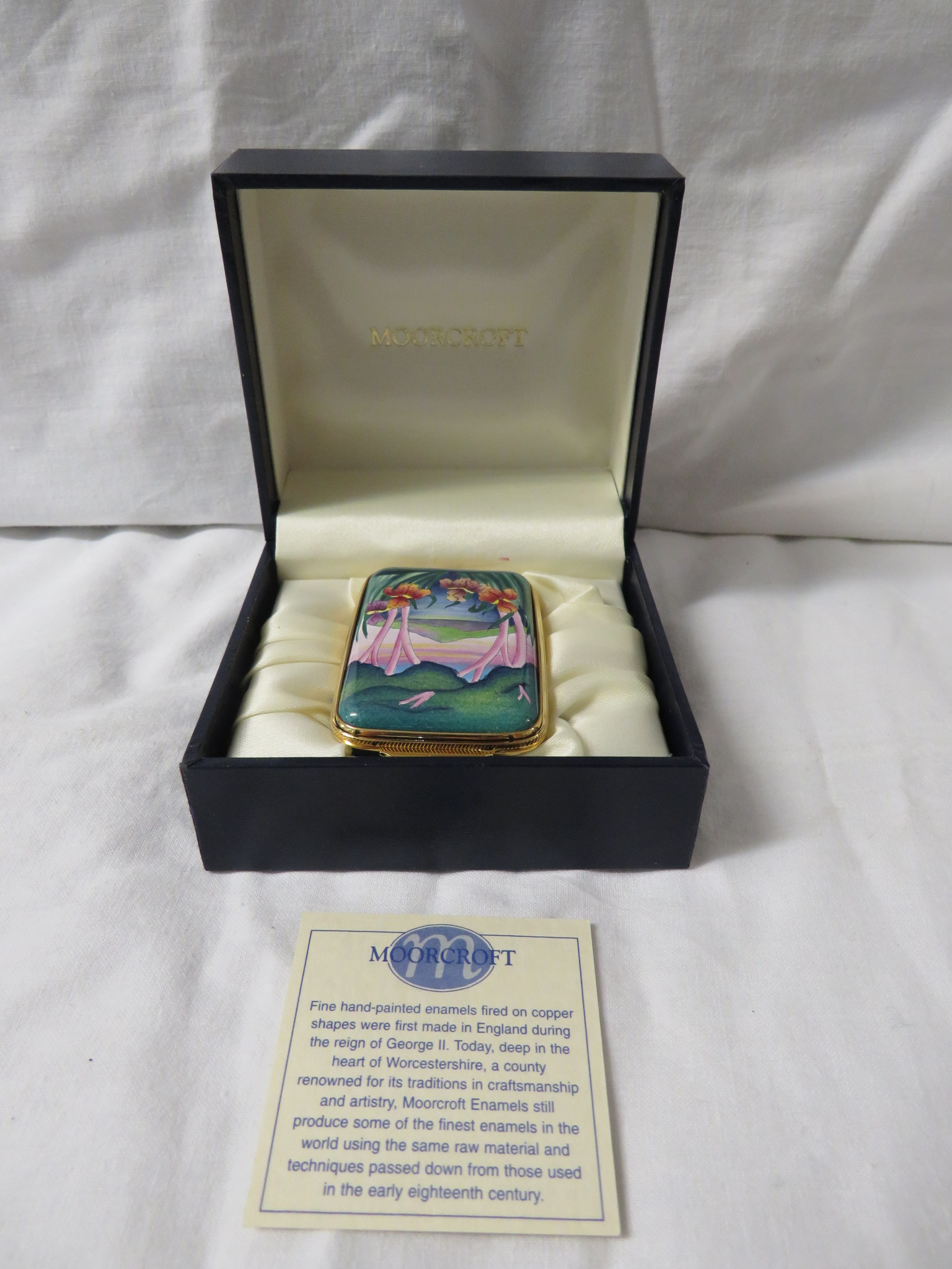 Lot 30 - Moorcroft enamel oblong pill box with hinged lid, blue body, the lid painted with landscape and