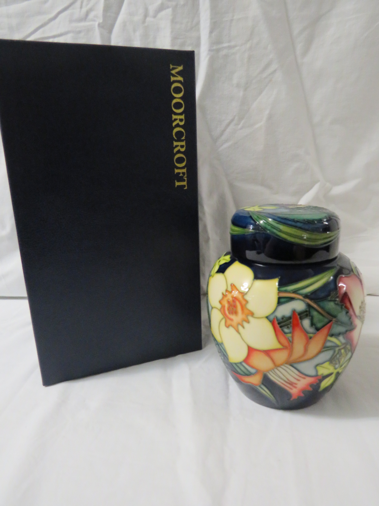 Lot 18 - Moorcroft pottery QEII Golden Jubilee ginger jar with cover, dark blue ground, tube lined decoration