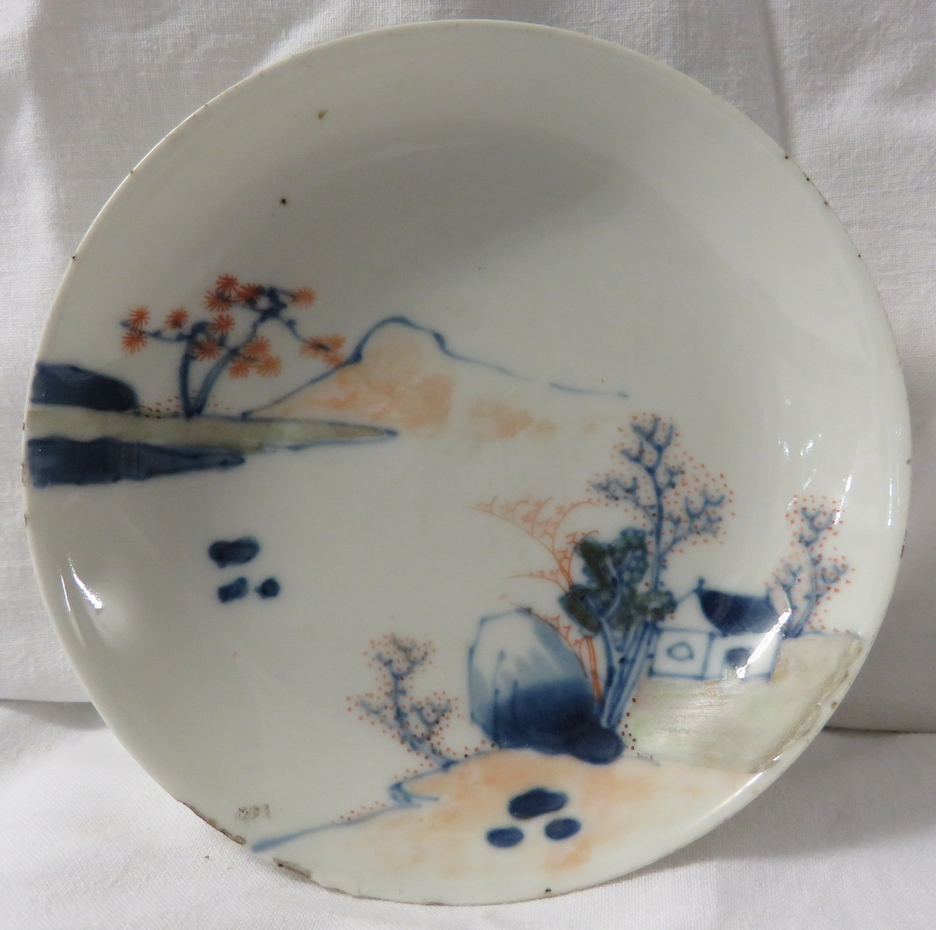 Lot 47 - A small Japanese porcelain dish painted with landscape in blue and red, diameter 11.5cm