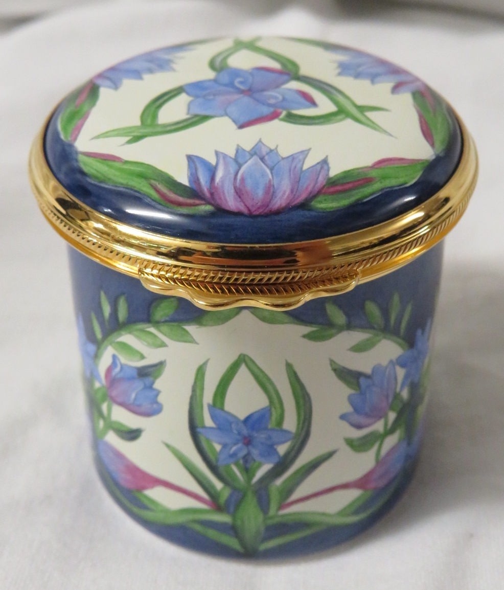 Lot 32 - Moorcroft enamel cylindrical pill box with hinged lid, blue ground and cream with panels of blue