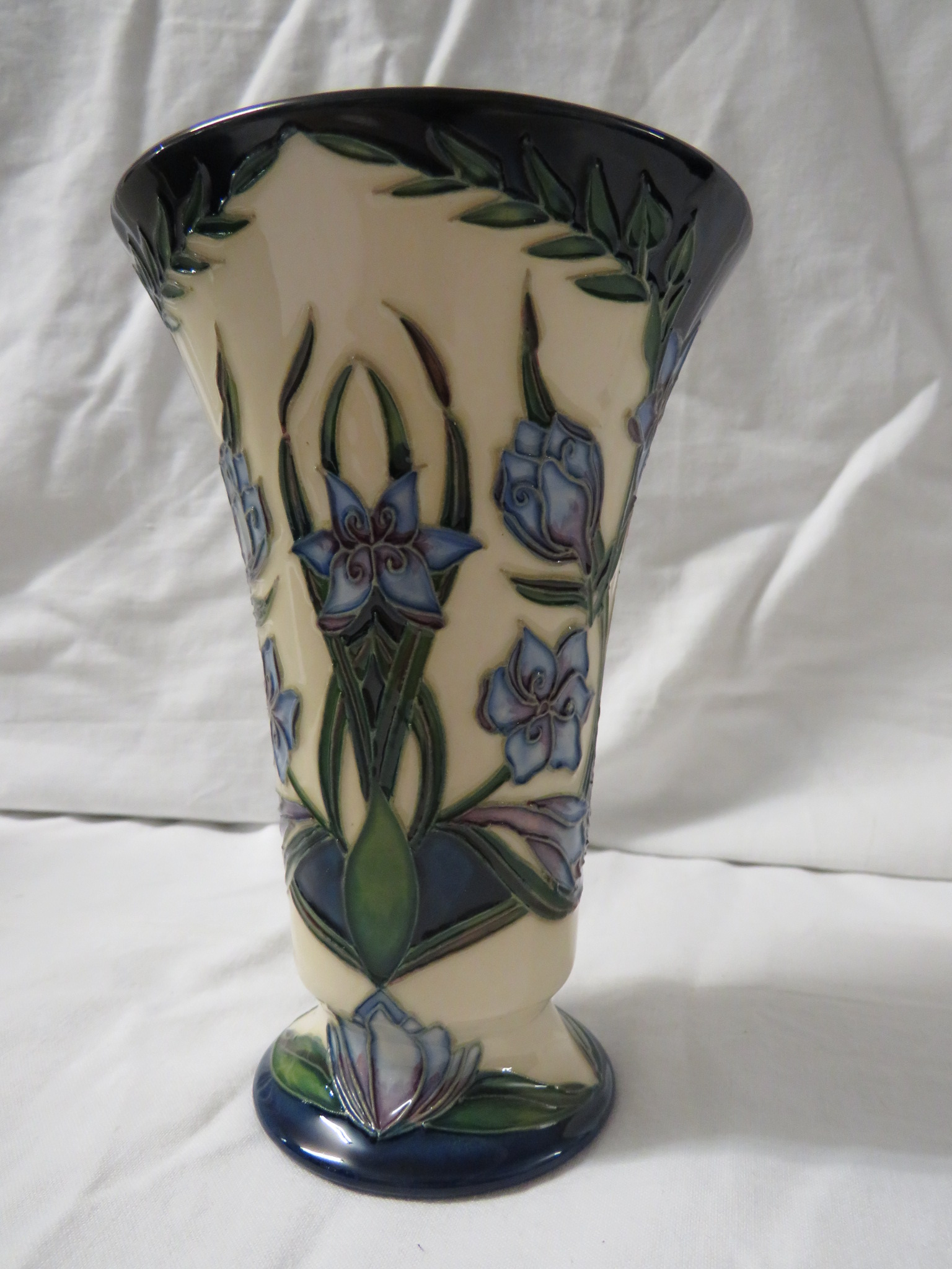 Lot 5 - Moorcroft pottery Kaffir Lily two star members vase with flared neck, cream ground, dark blue at