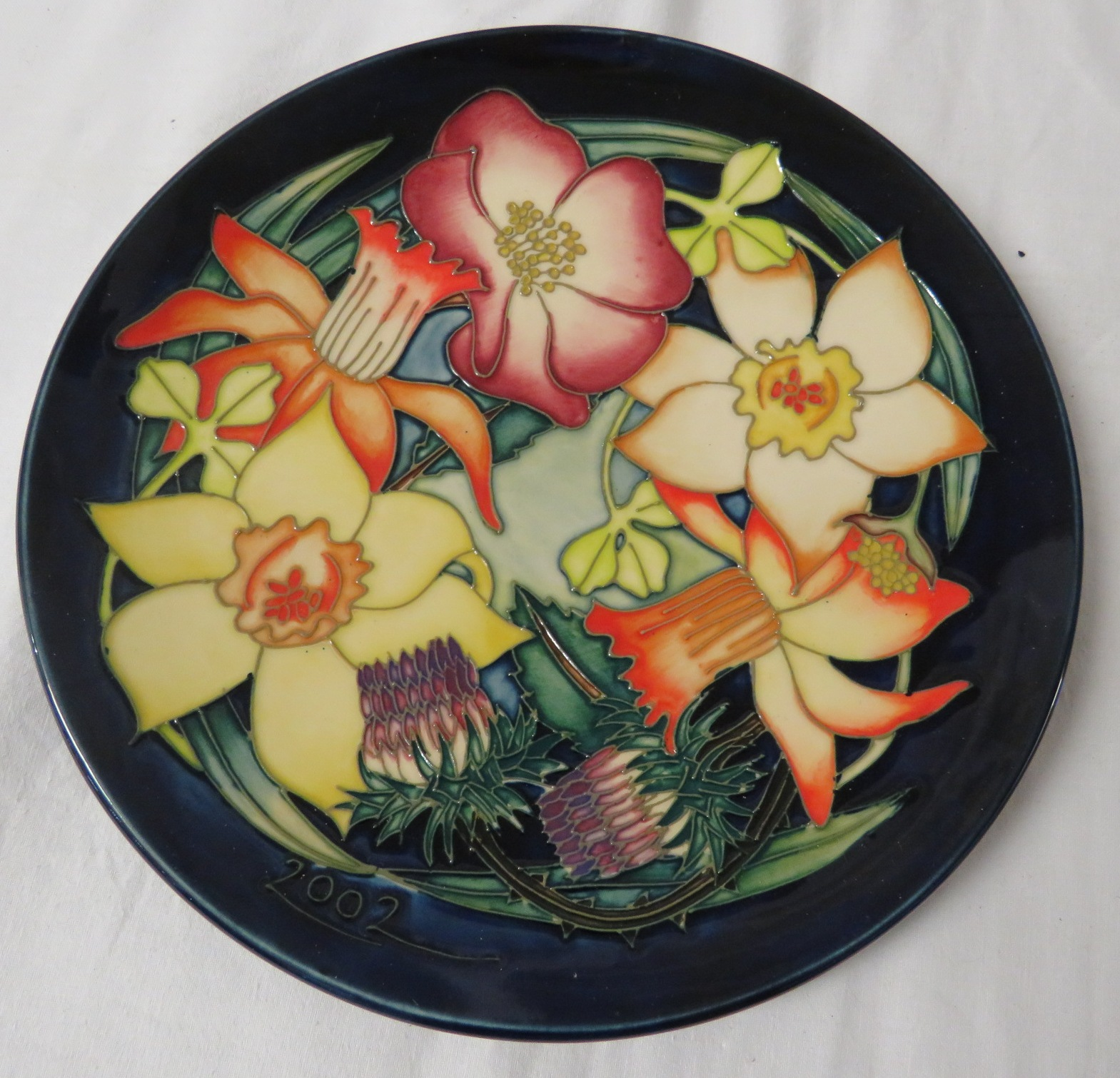 Lot 20 - Moorcroft pottery QEII Golden Jubilee plate, dark blue ground, tube lined decoration of variously