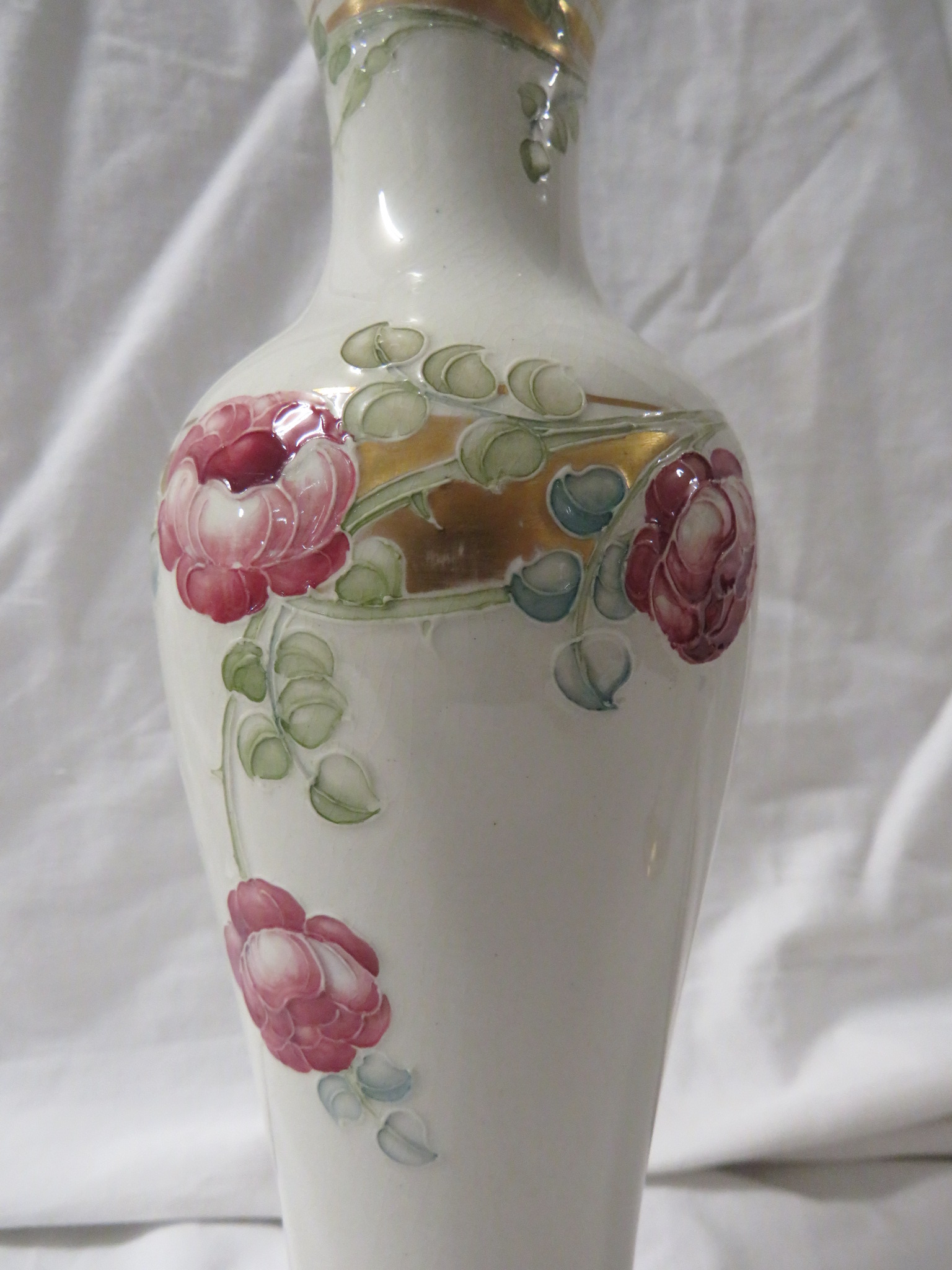 Lot 29 - A pair of William Moorcroft Macintyre slender baluster vases, cream ground with pink flowers and