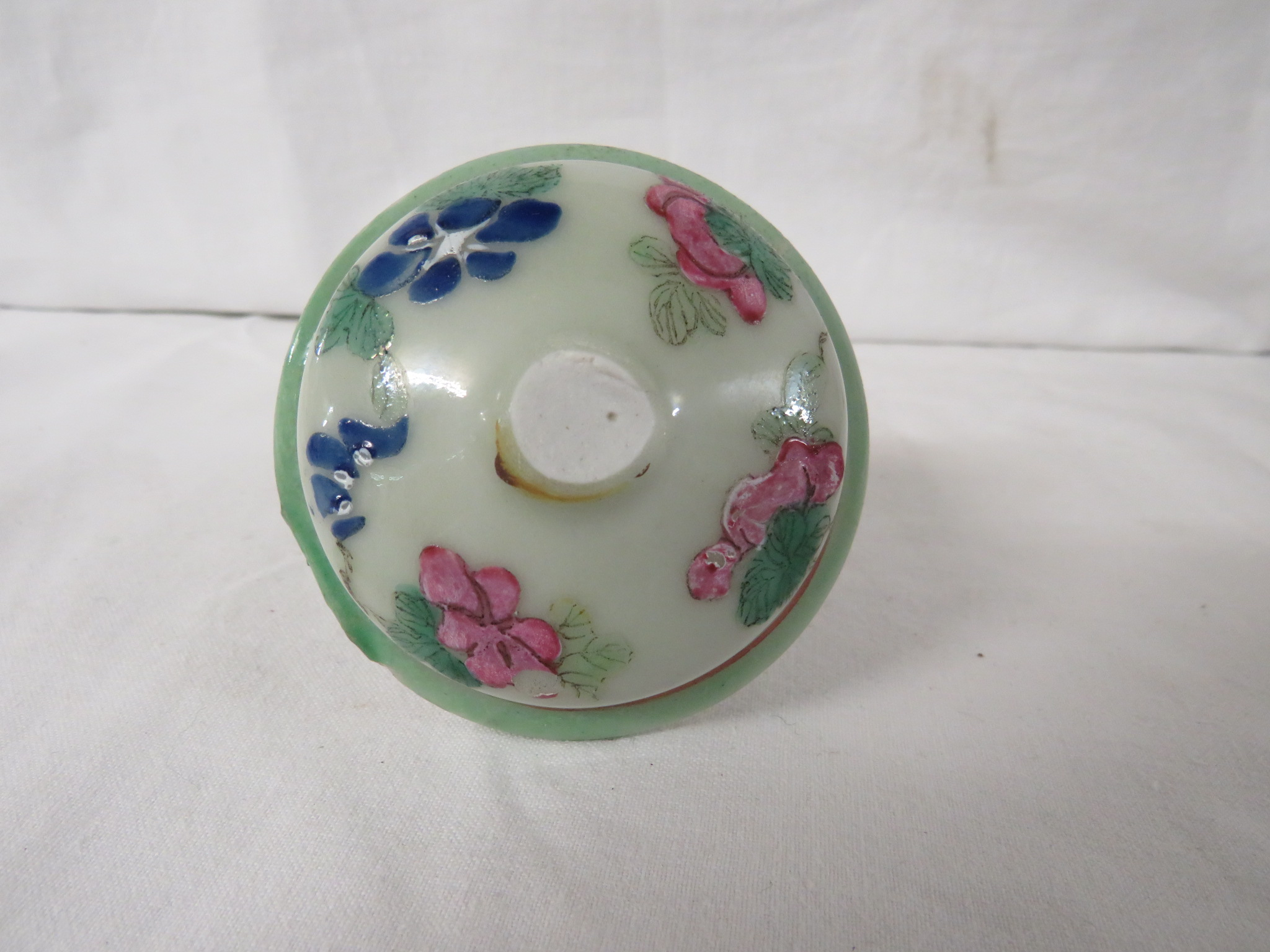 Lot 50 - A Chinese porcelain bottle vase with stopper, celadon ground, enamelled in the famille rose