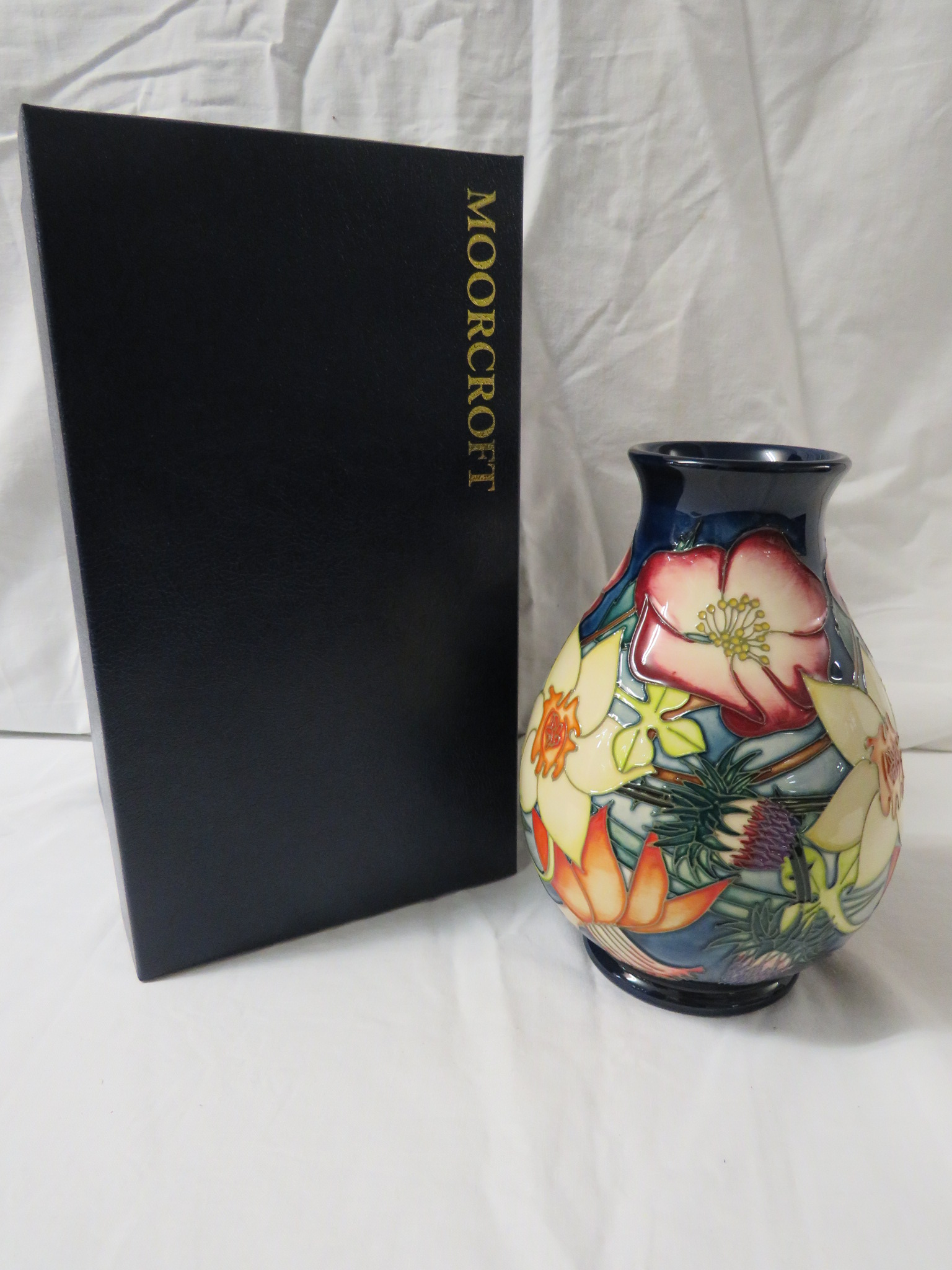 Lot 16 - Moorcroft pottery QEII Golden Jubilee ovoid vase, dark blue ground, tube lined decoration of
