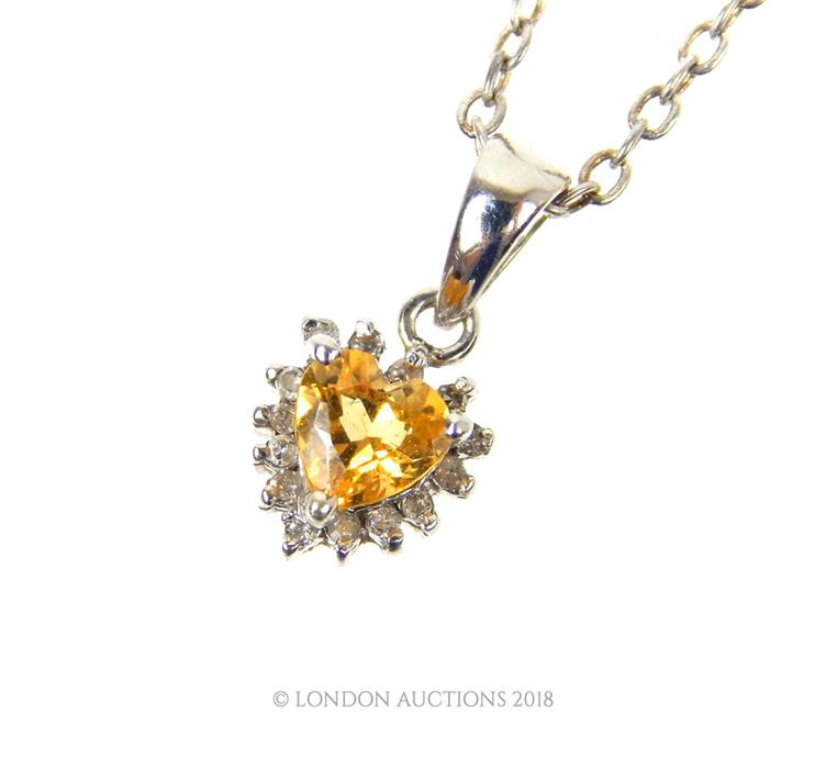 Lot 11 - A 14 ct white gold, heart shaped, citrine and diamond pendant necklace.
