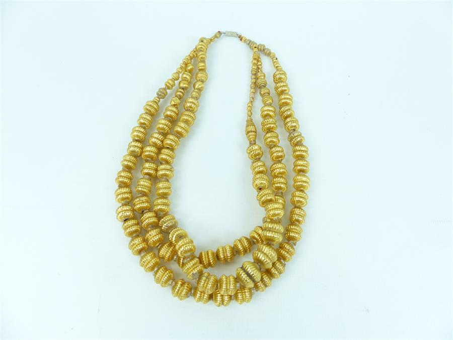 Lot 7 - A gold-coloured necklace with three strands