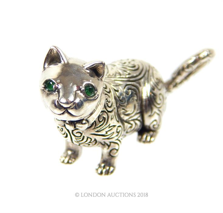 Lot 41 - A cast silver figure of a cat with emerald eyes.