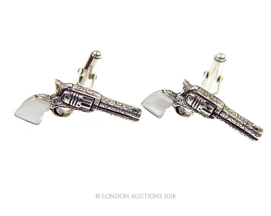 Lot 29 - A pair of silver cuff-links in the shape of pistols with mother of pearl handles